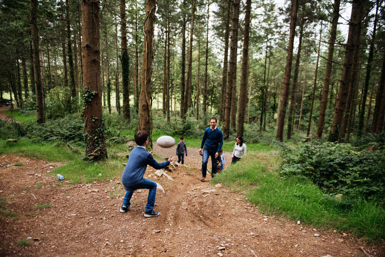 family in the woods throwing a ball