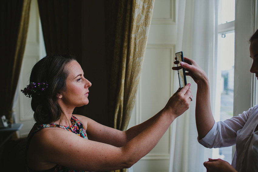 Bride looking into mirror at Royal Marine Hotel in Dun Laoghaire