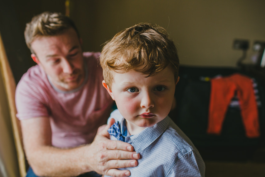father getting son ready on morning of wedding