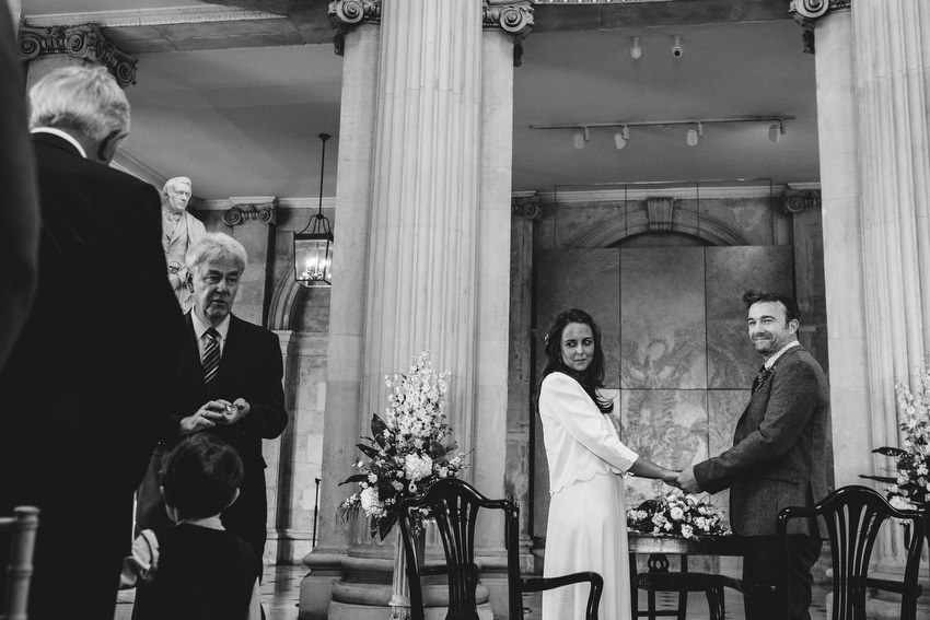 boy holds hands watching bride and groom get married at dublin city hall