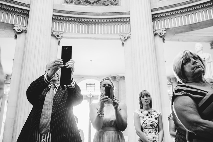 guests on phones at a wedding in dublin city hall
