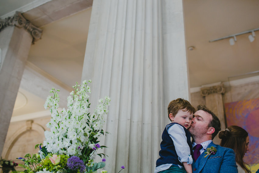 father kisses his son at a wedding in dublin city hall