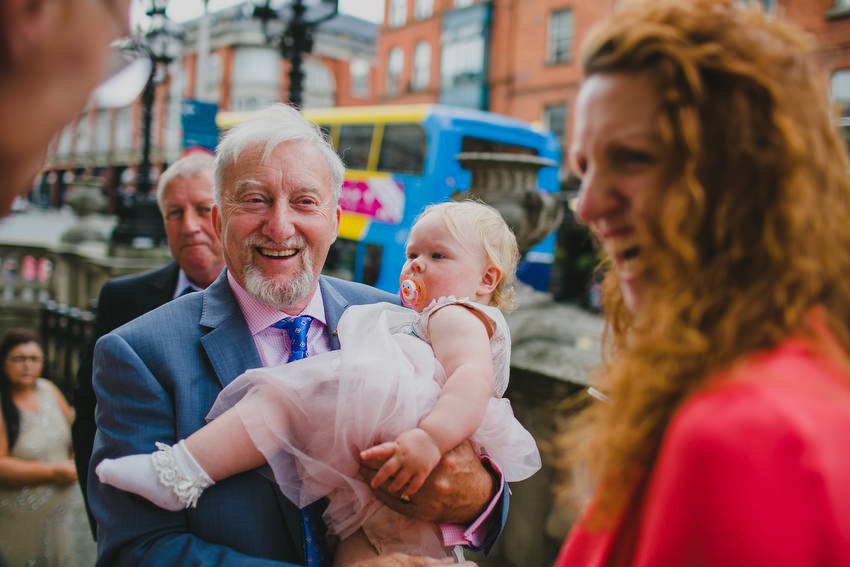 guests and small baby leaving wedding at dublin city hall