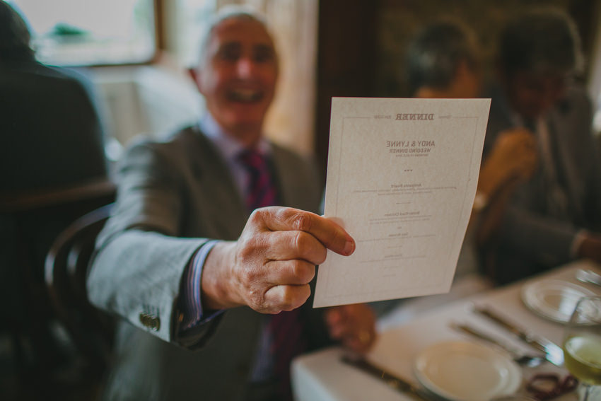 wedding guests reads menu at oliveto restaurant in dun laoghaire