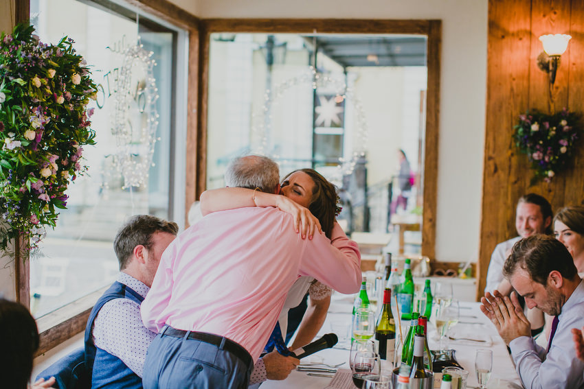father of the groom gets a hug from the bride after the  wedding speeches