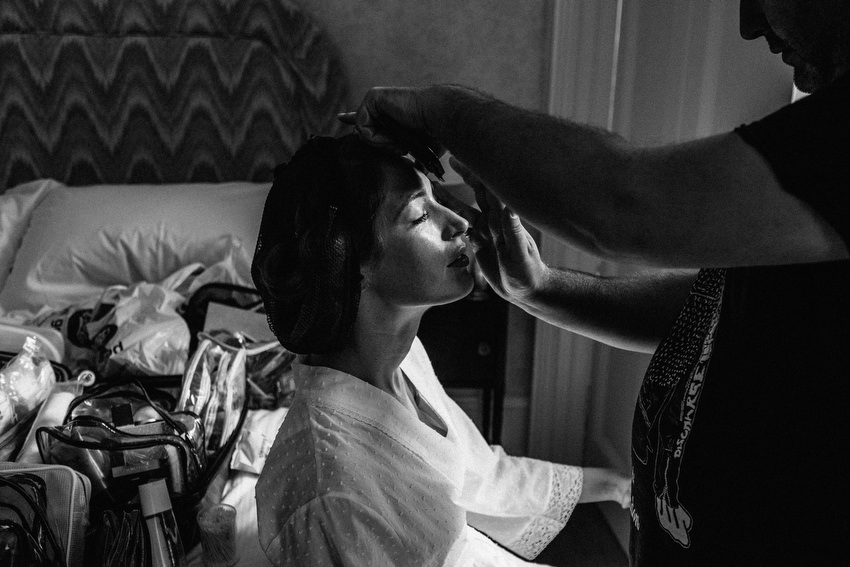 black and white of bride getting makeup at ballyvolane house