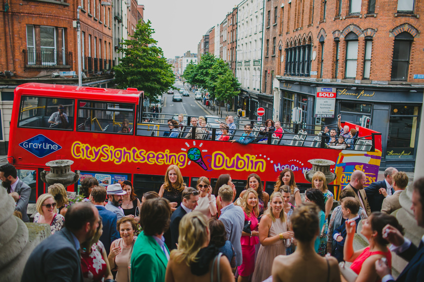 city sightseeing bus drives past wedding at dublin city hall