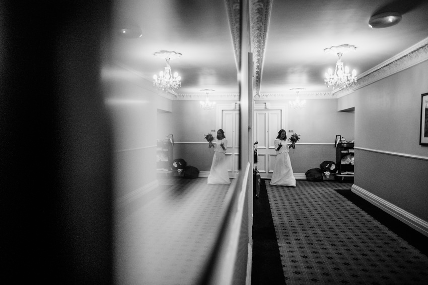 mirror image of bride coming down hall way in black and white
